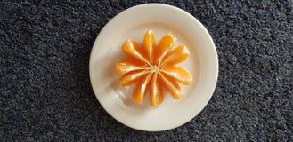 Bielu talerz z obranym mandarynka plasterk?w stojakiem na zmrok powierzchni obrazy royalty free