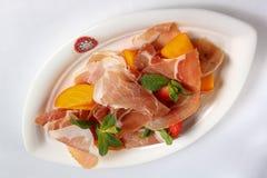 Bielu talerz z smakowitym mięsem przekąsza na bielu stole Obraz Royalty Free