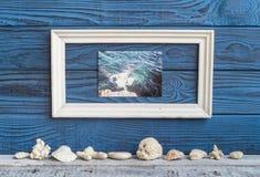 Bielu whith ramowy foto i skorupy na tle błękitne deski Obraz Stock