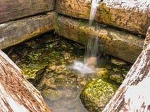 Bien con el agua de manatial pura en un lugar santo Foto de archivo