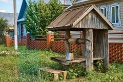 Bien de madera viejo demasiado grande para su edad con la hierba Imagen de archivo libre de regalías