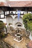 Bien en el patio en el castillo del salvado Ciudad del salvado en Rumania Fotos de archivo