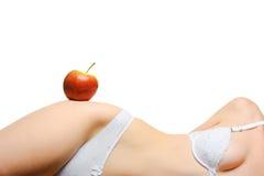 Bien proporcionado femenino una carrocería y una manzana roja Foto de archivo