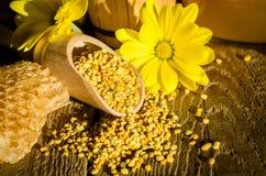 Bienenblütenstaubkörnchen in der hölzernen Schaufel, in den Bienenwaben und in den Blumen Stockfoto