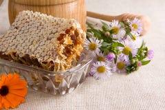 Bienenwabe, Blumen und Honig im Glas auf Sack Lizenzfreies Stockfoto