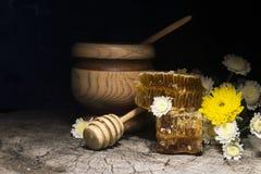 Bienenwaben und Blumen auf hölzernem Hintergrund Stockfotos