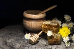 Bienenwaben und Blumen auf hölzernem Hintergrund Lizenzfreie Stockbilder