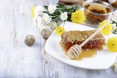 Bienenwaben und Blumen auf weißem hölzernem Hintergrund Lizenzfreie Stockbilder