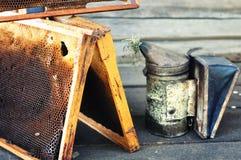 Bienenwaben und Imker bearbeiten die Herstellung des Rauches auf der Bank nahe der Wand Stockfoto