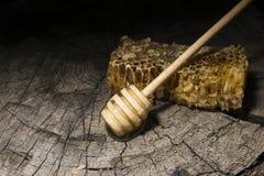 Bienenwaben und Stock zum Honig auf hölzernem Hintergrund Stockbild