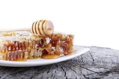 Bienenwaben und Stock zum Honig auf weißem Hintergrund Stockbilder