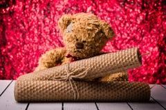 Bienenwachskerzen und -Teddybär betreffen nettes rotes Hintergrund bukeh Stockfoto