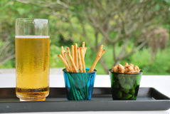 Bier, Acajounüsse im grünen Glas und Snack Stockbild