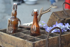 Bier. Beautiful old bier box made out of old wood with two old brown bottles out of glass and flower Stock Photos