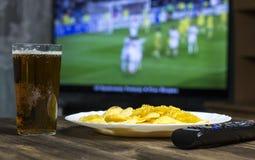 Bier, Chips, Fernsehfernbedienung und in denen Fernsehen Showfußballspiel Lizenzfreie Stockfotografie