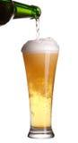 Bier, das aus Flasche in Glas gießt Stockfotos