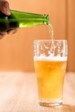 Bier, das aus Spitze in der Flasche auf hölzerner Tabelle gießt Lizenzfreie Stockbilder
