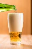 Bier, das aus Spitze in der Flasche auf hölzerner Tabelle gießt Lizenzfreies Stockfoto