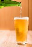 Bier, das aus Spitze in der Flasche auf hölzerner Tabelle gießt Stockfotos