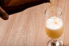 Bier, das aus Spitze in der Flasche auf hölzerner Tabelle gießt Stockbilder
