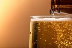Bier, das aus Spitze in der Flasche auf hölzerner Tabelle gießt Lizenzfreie Stockfotografie