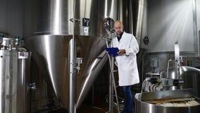 Bier, das an der Brauerei macht Der Angestellte der Brauereikontrollen die Ausrüstung Funktionierende Maschine des Wartungsarbeit stock footage