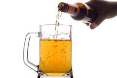 Bier, das unten aus einer Flasche gießt stockbild