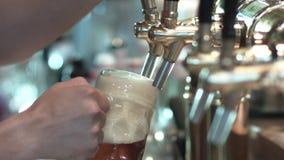 Bier in een mok met een kraan wordt gegoten die stock footage