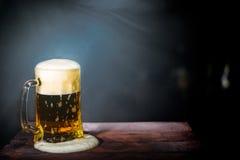 Bier in einem Becher auf einem dunklen Hintergrund stockfoto