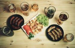 Bier, geroosterde aardappel en pannen met geroosterde worsten Royalty-vrije Stock Fotografie