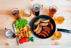 Bier, geroosterde aardappel en geroosterde worsten Stock Foto's