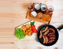 Bier, geroosterde aardappel en geroosterde worsten Hoogste mening Royalty-vrije Stock Fotografie