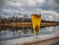 Bier in glas op houten lijst tegen blauwe hemel en wolken op natuurlijke achtergrond met bokeh Royalty-vrije Stock Fotografie