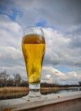 Bier in glas op houten lijst tegen blauwe hemel en wolken op natuurlijke achtergrond met bokeh royalty-vrije stock afbeeldingen