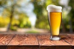 Bier in glas op houten lijst tegen groen Royalty-vrije Stock Afbeelding