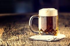 Bier Goldenes Bier des Entwurfs im Glasgefäß Entwurfsale mit Schaum auf die Oberseite Kaltes Bier auf sehr altem Eichenbrett Stockfotos