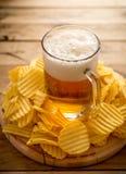 Bier im Becher, Chips, hölzerner Hintergrund, Komfortlebensmittel lizenzfreies stockfoto