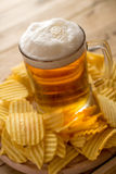Bier im Becher, Chips, hölzerner Hintergrund, Komfortlebensmittel stockbild