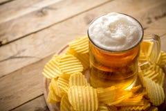 Bier im Becher, Chips, hölzerner Hintergrund, Komfortlebensmittel stockfotografie