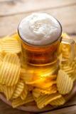 Bier im Becher, Chips, hölzerner Hintergrund, Komfortlebensmittel stockbilder