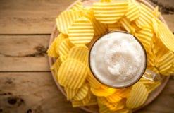 Bier im Becher, Chips, hölzerner Hintergrund, Komfortlebensmittel Stockfotos