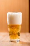 Bier im Glas, auf hölzernem Hintergrund Lizenzfreie Stockfotografie
