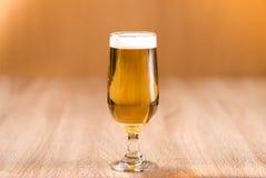 Bier im Glas auf hölzerner Tabelle Stockfotografie