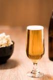 Bier im Glas auf hölzerner Tabelle Stockbild