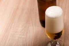 Bier im Glas auf hölzerner Tabelle Stockbilder