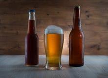 Bier im Glas und in den Flaschen lizenzfreie stockbilder