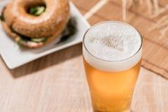 Bier im Glas und im Burger auf hölzerner Tabelle Stockbilder