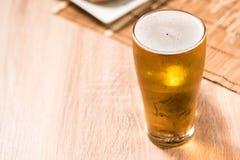 Bier im Glas und im Burger auf hölzerner Tabelle Stockfotografie