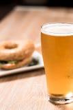 Bier im Glas und im Burger auf hölzerner Tabelle Lizenzfreie Stockbilder