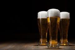 Bier mit drei Gläsern auf hölzerner Tabelle Lizenzfreie Stockfotos